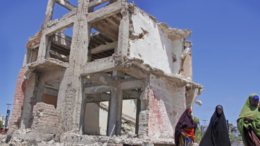 Somali women walk past a destroyed building after a suicide car bomb attack in the capital Mogadishu, Somalia.