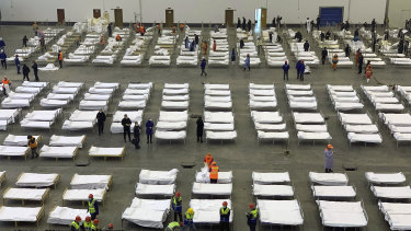 Workers arrange beds in a convention center that has been converted into a temporary hospital in Wuhan, China.