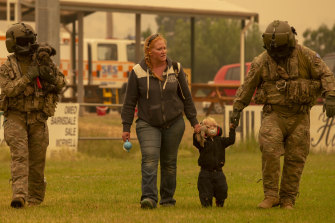 Two Australian Army soldiers help people evacuate onto a Chinook helicopter at Omeo showgrounds in Victoria on Sunday.