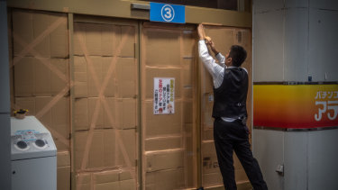 A man covers over a doorway ahead of the arrival of Typhoon Hagibis.