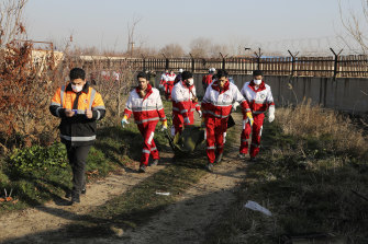 Rescue workers carry the body of a victim of the Ukraine International Airlines flight that was shot down.
