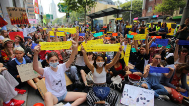 Student activists from School Strike for Climate Australia (SS4C) hold a 'Solidarity Sit-down' outside the office of the Liberal Party in Sydney, on Friday.