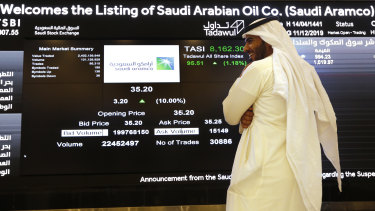 A Saudi stock market official smiles as he watches the stock market screen displaying Saudi Arabia's state-owned oil company Aramco after its trading debut.