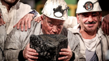 Miners kiss the last piece of coal during a farewell event for the German hard coal mining industry in 2018.