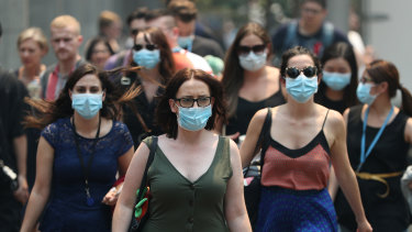 People wear face masks to protect from smoke haze as they cross a busy street in Sydney's CBD.