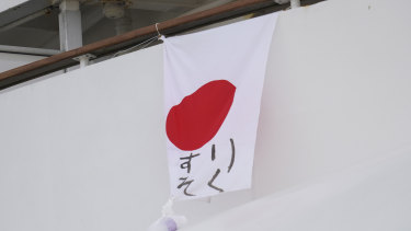 """A Japanese flag with the message """"Lack Medicine"""" written on it hangs from the Diamond Princess cruise."""