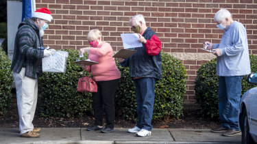 People wait in line on the first day of advance voting for Georgia's two Senate runoff elections.
