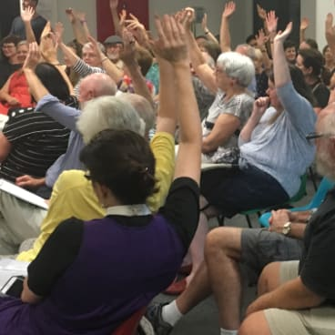 More than 50 residents raise their hands to indicate support for a boycott of the the Pig 'N' Whistle pub.
