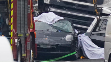 The black Porsche under the semi-trailer after the crash.