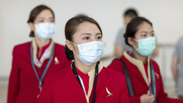 People wearing face masks to protect themselves from coronavirus are seen at Brisbane International Airport.