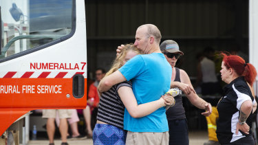 People embrace at the Numeralla Rural Fire Brigade station near where the location of the aircraft's crash.