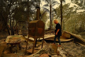 Anna Dunne walks through the remains of her home on the outskirts of Nelligen where several homes and buildings were destroyed or damaged in the fire near Batemans Bay on New Year's Eve,