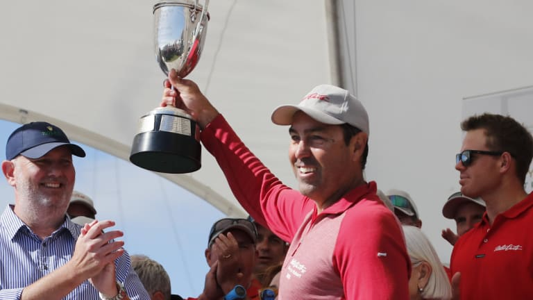 Triumphant: Mark Richards hoists the J.H. Illingworth trophy after Wild Oats XI arrived in Hobart.