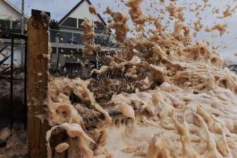 Foam explodes over the fences of beachside properties in Collaroy.
