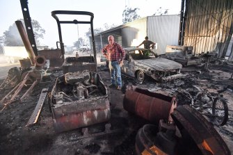 Peter Riley (front) and his son-in-law Simon Evvage at their fire damaged Clifton Creek property in Victoria.