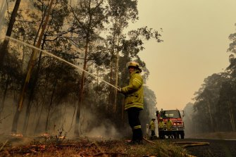 Fire crews fight to contain a blaze on the Princes Highway between the NSW towns of Nowra and Batemans Bay on Sunday.