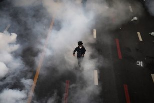 An anti-government protester flees a cloud of tear gas during protests in Bangkok on Saturday.