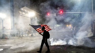 A Black Lives Matter protester carries an American flag as teargas fills the air in Portland.