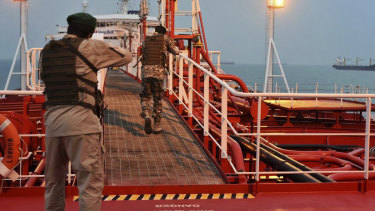 Two armed members of Iran's Revolutionary Guard inspect the British-flagged oil tanker Stena Impero in July. Tensions have flared again after the assassination of Qassem Soleimani by the US.