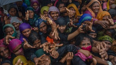 Rohingya Muslim women, who crossed over from Myanmar into Bangladesh, stretch their arms out to collect sanitary products distributed by aid agencies near Balukhali refugee camp, Bangladesh.