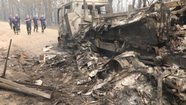 The firefighters return to the site where their trucks were overrun.