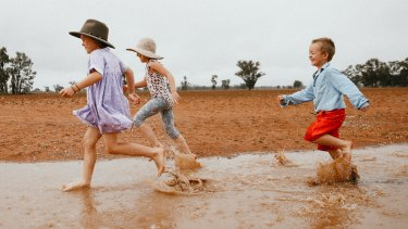 Dolly, 7, Daisy, 5, and Trader Paine, 4, enjoy welcome rain in Narromine last month. Here's to more of the same.