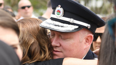 RFS Commissioner Shane Fitzsimmons hugs Melissa O'Dwyer, the wife of NSW RFS volunteer Andrew O'Dwyer, during his funeral service.