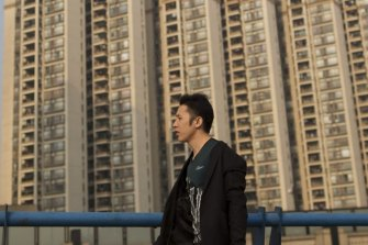 A man walks past residential buildings in the Pazhou district of Guangzhou, Guangdong Province, China.