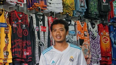 Muhammad Bakri in his shop in Kuta selling knock off AFL shirts and decorated helmets.