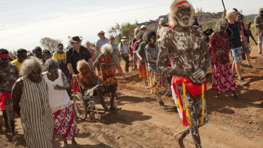 In 2011, East Arnhem Chief Lawyer Jacob Nayinggul is pushed in his wheelchair by ANU historian Martin Thomas as he oversees proceedings as human remains are eventually returned to their ancestral home in Gunbalanya, Arnham Land.