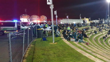 Ambulance officers attending to two people who were shot at Perth Motorplex on Saturday night.